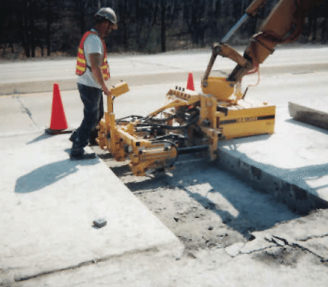 E-Z Drill concrete dowel pin drill mounted to excavator for full depth repair